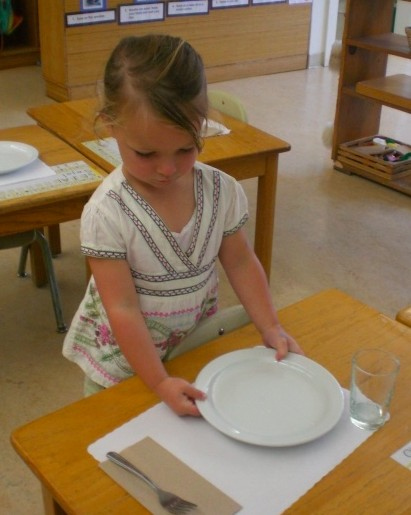 A South Class student practices setting her table for lunch.