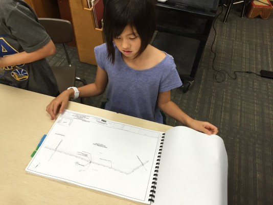 Third Grader Sami, with plans for the marsh restoration.